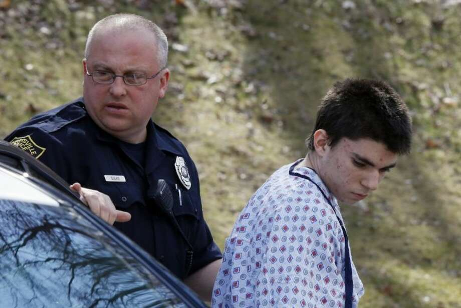 Alex Hribal, the suspect in the multiple stabbings at the Franklin Regional High School in Murrysville, Pa., is escorted by police to a district magistrate to be arraigned on Wednesday, April 9, 2014, in Export, Pa. Authorities say Hribal has been charged after allegedly stabbing and slashing at least 19 people, including students, in the crowded halls of his suburban Pittsburgh high school Wednesday. Photo: Keith Srakocic