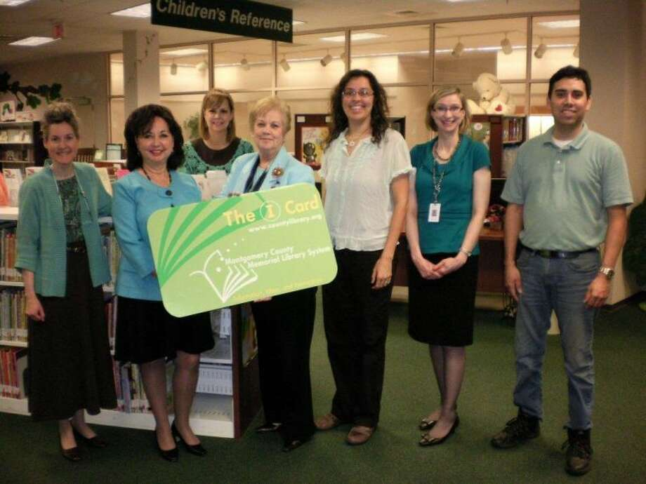 MCMLS Library Administration poses with the giant library card. Shown left to right: Rhonda DeLuish, Lana Beathard, Laura Robinson, Jerilynn Williams, Melissa Baker, Sarah Booth, and Tim Alcala.