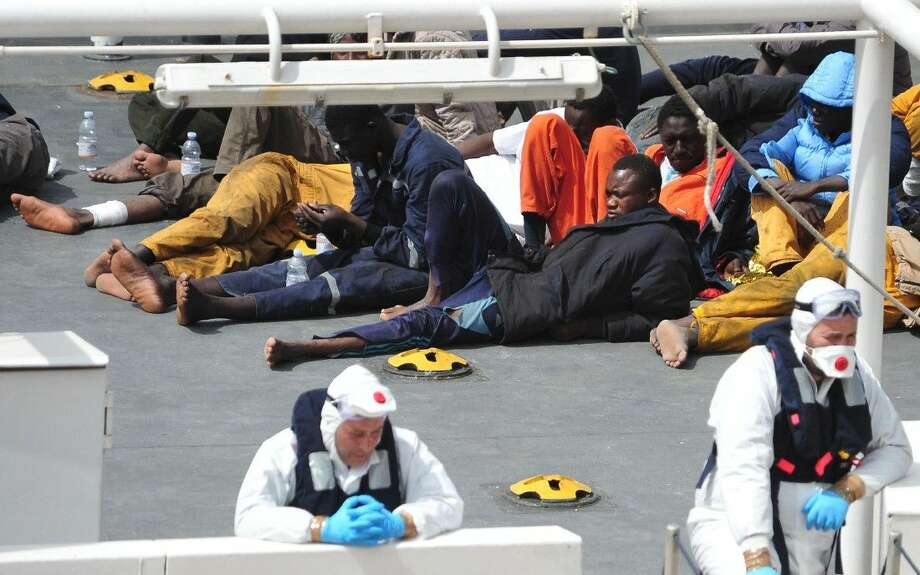 Survivors of the smuggler's boat that overturned off the coasts of Libya lie on the deck of the Italian Coast Guard ship Bruno Gregoretti, in Valletta's Grand Harbour Monday. A smuggler's boat crammed with hundreds of people overturned off Libya's coast on Saturday as rescuers approached, causing what could be the Mediterranean's deadliest known migrant tragedy. Photo: Lino Azzopardi