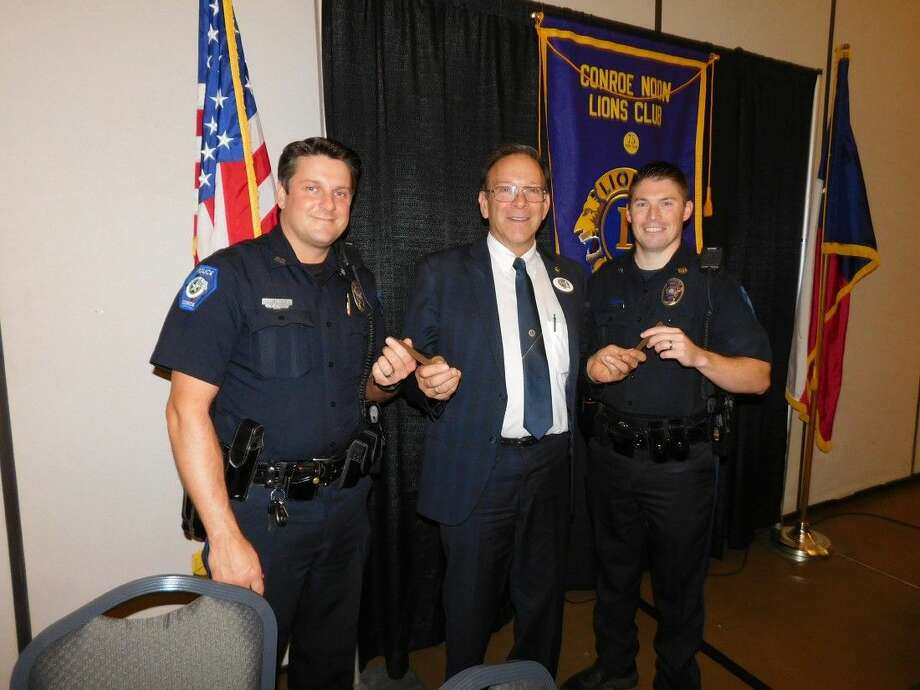 Club President Karl Johnson, center, thanks two of Conroe's finest; Officer Jeremy Whatley, left, and Officer Tyson Sutton, right, with a coveted Conroe Noon Lions Club pen for bringing the CPD K-9 unit to the club meeting last week.