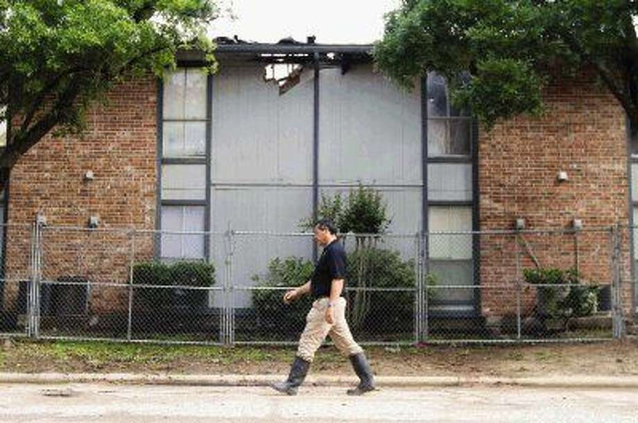 A man with Gemstar with Apartment Construction walks by the fire damaged unit 11 section of the Bellshire Apartments in Conroe Wednesday.