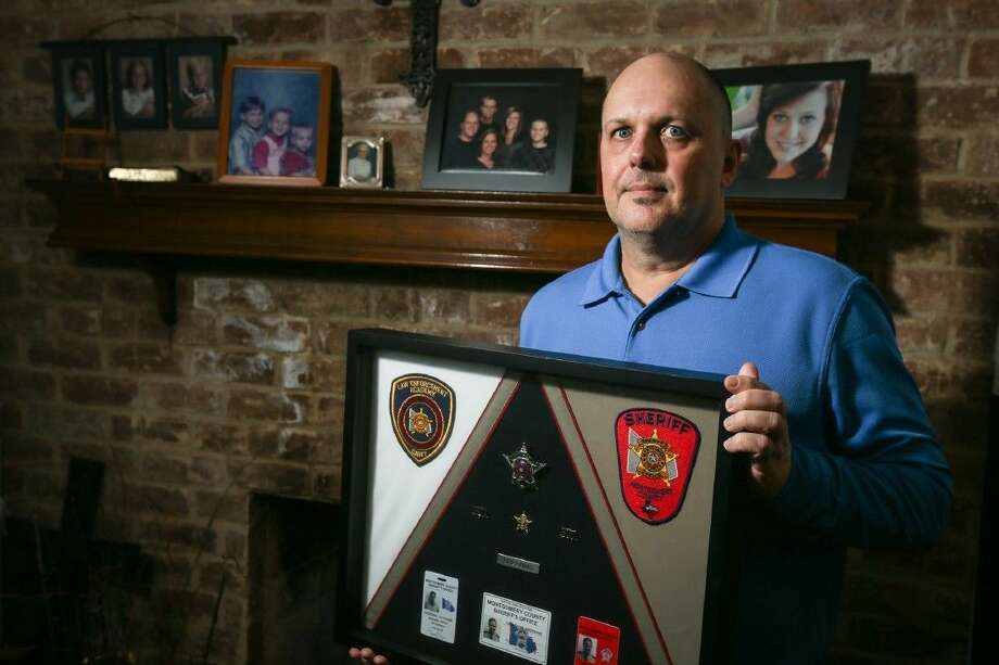 Steve Breeding, father of Catherine Breeding, a Montgomery County Sheriff's deputy who was killed in a drunk driving incident, displays various framed objects owned by his daughter on Friday at their home in Shenandoah. Photo: Michael Minasi
