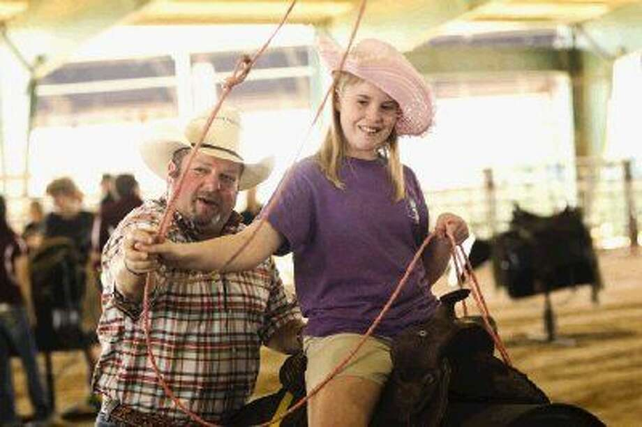 Kate Wimberly, of Conroe, learns how to rope a steer during the inaugural Special Angels Rodeo at the Montgomery County Fairgrounds Equestrian Center Sunday. Photo: Michael Minasi