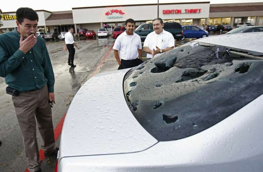 Pablo Loza, left, looks at damage to his car which took a beating during a hailstorm while parked in a lot outside a thrift store, Thursday, April 3, 2014, in Denton, Texas. Severe thunderstorms in North Texas on Thursday spawned a reported tornado in one town and pummeled Denton with hail as large as softballs.