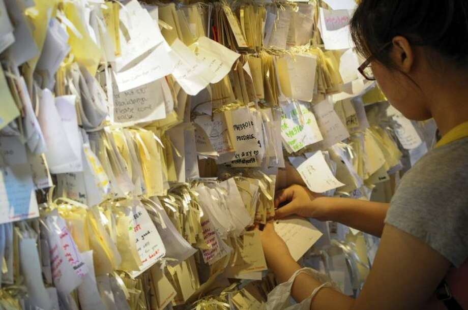 A woman ties a message card for passengers onboard the missing Malaysia Airlines Flight 370 at a shopping mall in Petaling Jaya, near Kuala Lumpur, Malaysia, Thursday, April 10, 2014. With hopes high that search crews are zeroing in on the missing Malaysian jetliner's crash site, ships and planes hunting for the aircraft intensified their efforts Thursday after equipment picked up sounds consistent with a plane's black box in the deep waters of the Indian Ocean. Photo: STR