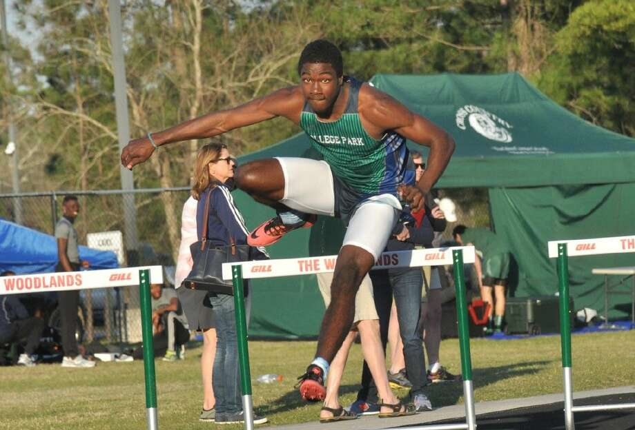 College Park's Joshua Holman clears a hurdle in the 300-meter hurdles at the Highlander Invitational track and field meet at The Woodlands High School earlier this season. Photo: Keith MacPherson