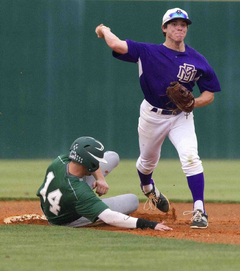 Montgomery shortstop Austin Cross tries to turn a double play in the second inning of a District 15-6A baseball game Thursday. Photo: Jason Fochtman