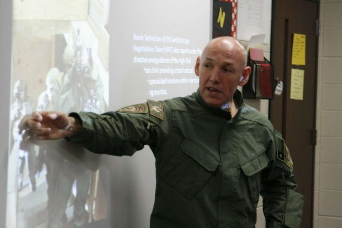 Michael Lovell with the Harris County Sheriff's Office Special Response Team shares the tactical team's duties when they are called out to assignment at Woodcreek Middle School's Career Day Dec. 20.
