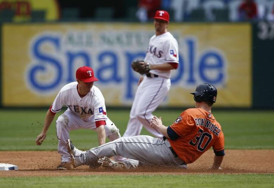 The Astros' Matt Dominguez, right, is tagged out on a stolen base attempt by the Rangers' Josh Wilson. The Rangers won 1-0. Photo: Jim Cowsert