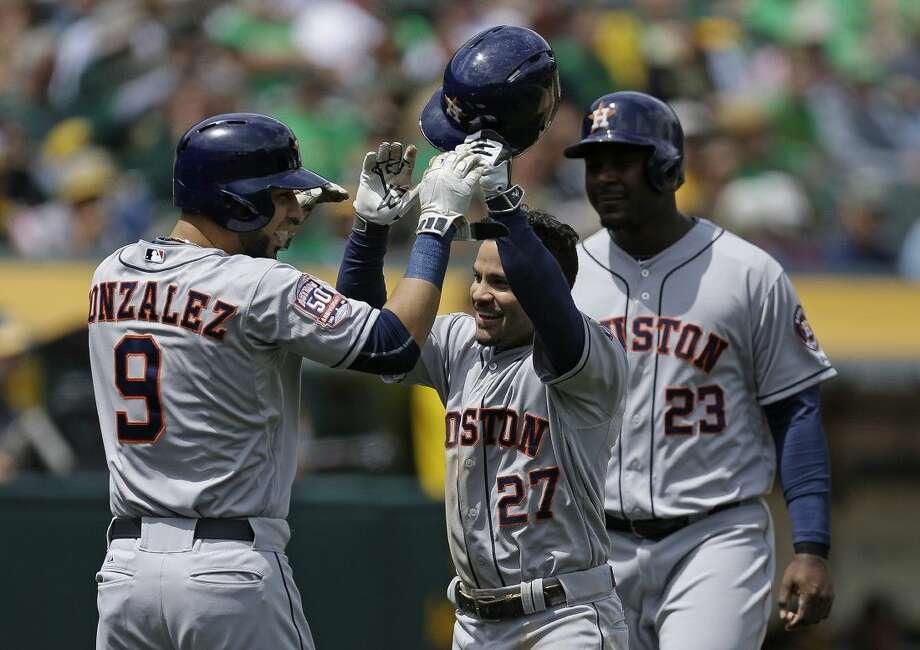 Houston Astros' Jose Altuve celebrates with Marwin Gonzalez and Chris Carter, right, after Altuve hit a three run home run Saturday in Oakland, Calif. Photo: Ben Margot