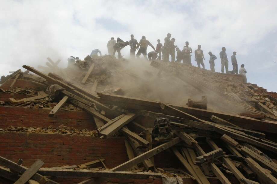 Volunteers help remove debris of a building that collapsed at Durbar Square, after an earthquake in Kathmandu, Nepal, Saturday. Photo: Niranjan Shrestha