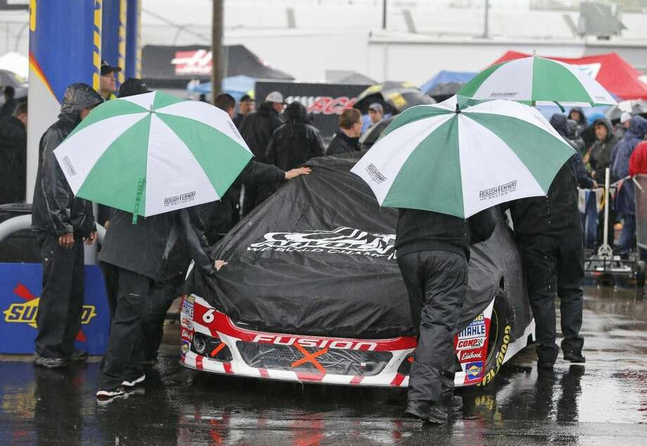 The crew for Trevor Bayne pushes his car to the inspection station as rain falls at Richmond International Raceway in Richmond, Va., Saturday. Photo: Steve Helber