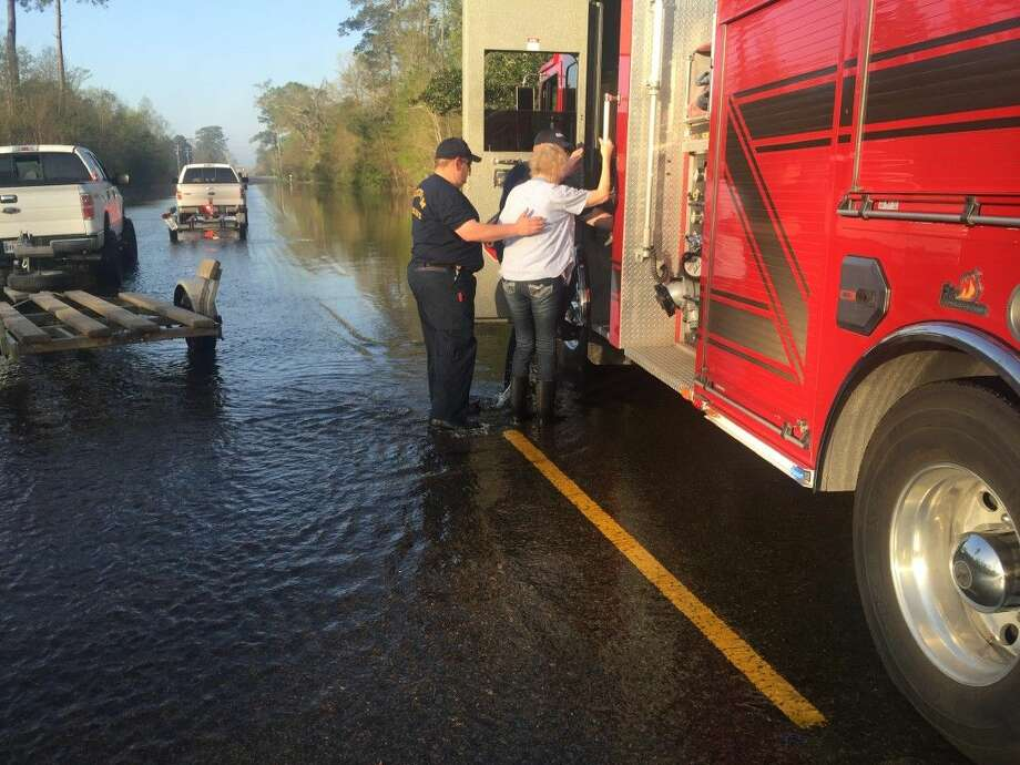 A firefighter with Needham FD helps a woman evacuate due to flooding in Southeast Texas. With residents flooded out of their homes due to a rising Sabine River in Southeast Texas, Montgomery County first responders are lending a helping hand to those in need.