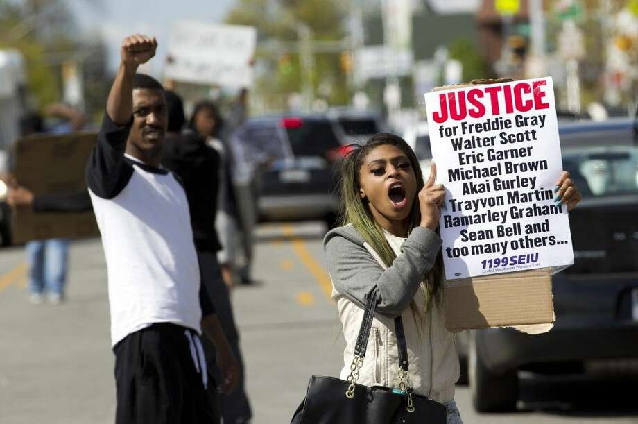 Caira Byrd hold support signs for Freddie Gray outside of Vaughn Greene Funeral Home, during his wake in Baltimore, Md. Sunday. Gray died from spinal injuries about a week after he was arrested and transported in a police van. Photo: Jose Luis Magana