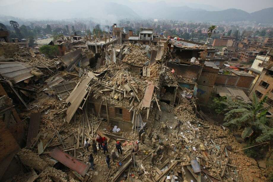 Rescue workers remove debris as they search for victims of earthquake in Bhaktapur near Kathmandu, Nepal Sunday. A strong magnitude earthquake shook Nepal's capital and the densely populated Kathmandu Valley before noon Saturday, causing extensive damage with toppled walls and collapsed buildings, officials said. Photo: Niranjan Shrestha