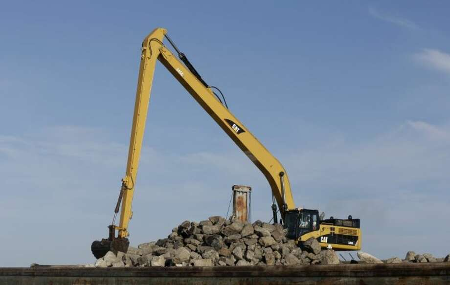 In this Oct. 29, 2013 file photo, a large excavator shovel scoops up limestone boulders to dump into the Gulf of Mexico to help rebuild an oyster reef off the Texas coast. The $5.4 million project will rebuild some 57 acres of reef, helping to revitalize the fragile Gulf marine ecosystem. U.S. Army Corps of Engineers spokesman Isidro Reyna said the 250 feet long and 50 feet wide structure was completed Saturday, April 12, 2014. Photo: Pat Sullivan