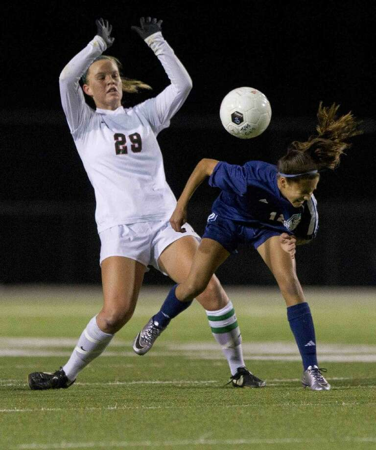 The Woodlands' Grace Piper, left, avoids a collision with Kingwood's Carly Stroud during the first period of a District 16-6A girls soccer game at Woodforest Bank Stadium Tuesday. To purchase this photos, and others like it; go to HCNpics.com. Photo: Jason Fochtman