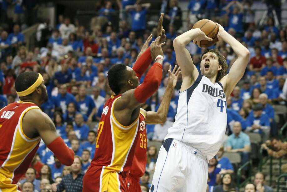 The Rockets' Josh Smith, left, and Dwight Howarddefend as Dallas forward Dirk Nowitzki shoots in Game 4 in Dallas. Photo: Tony Gutierrez