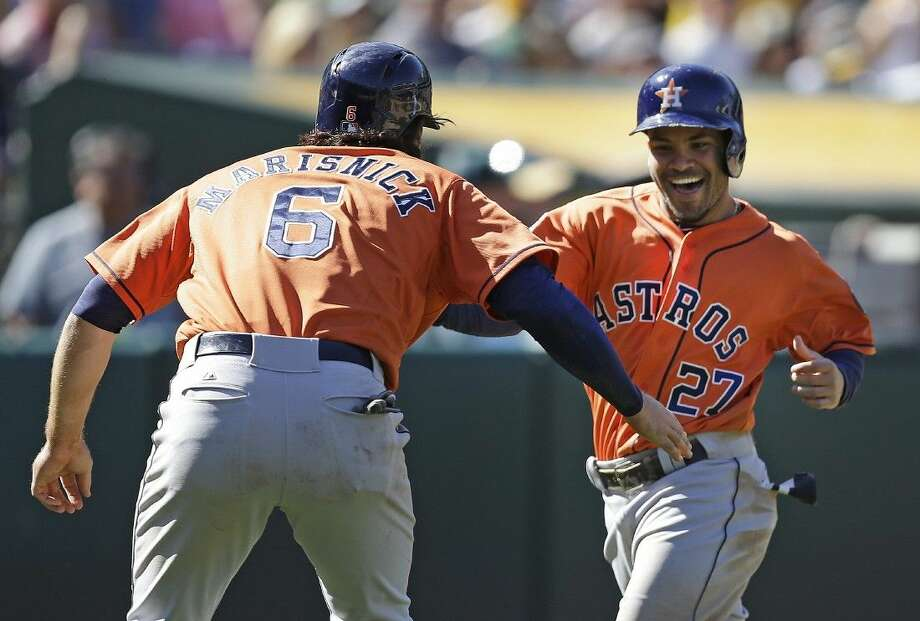 Astros teammates Jose Altuve, right, and Jake Marisnick celebrate as they score in the ninth inning. Photo: Ben Margot