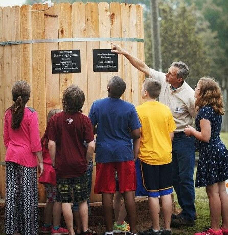 4th and 5th grader students at Bear Branch Elementary School in Magnolia learn about the rainwater harvesting system installed at their school from JMG volunteer Jim Bunscho.