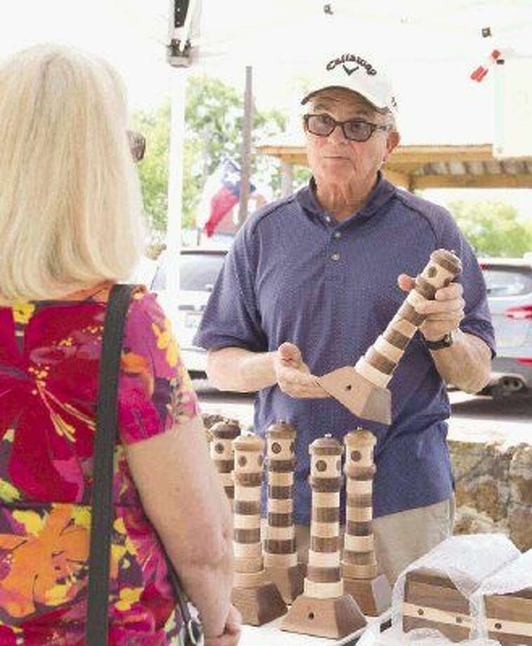 Jimmy Chilcutt talks to a customer about various puzzle boxes he sells at the Antique Festival in downtown Montgomery. Photo: Jason Fochtman