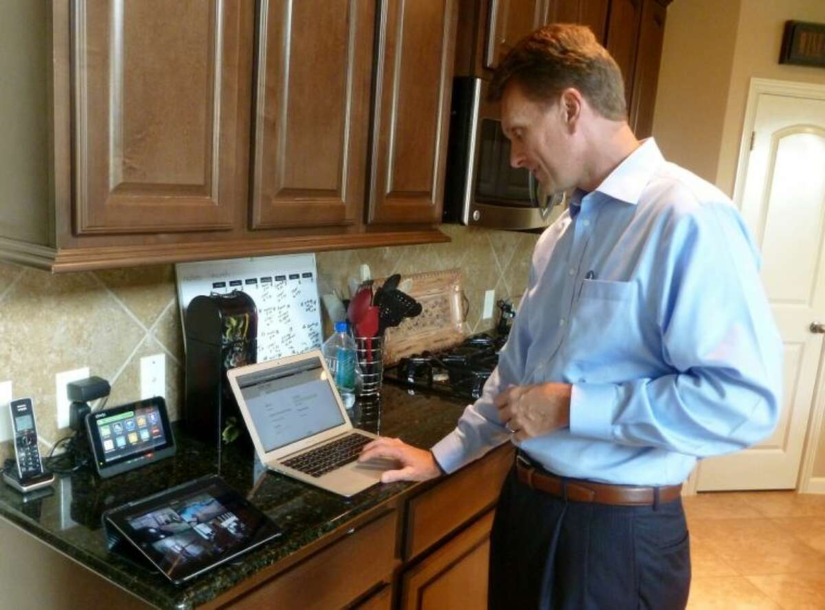 Mitch Bowling, senior vice president and general manager of New Business for Comcast Cable Corporation, shows how a complete home security system can be controlled on a tablet, laptop and phone.
