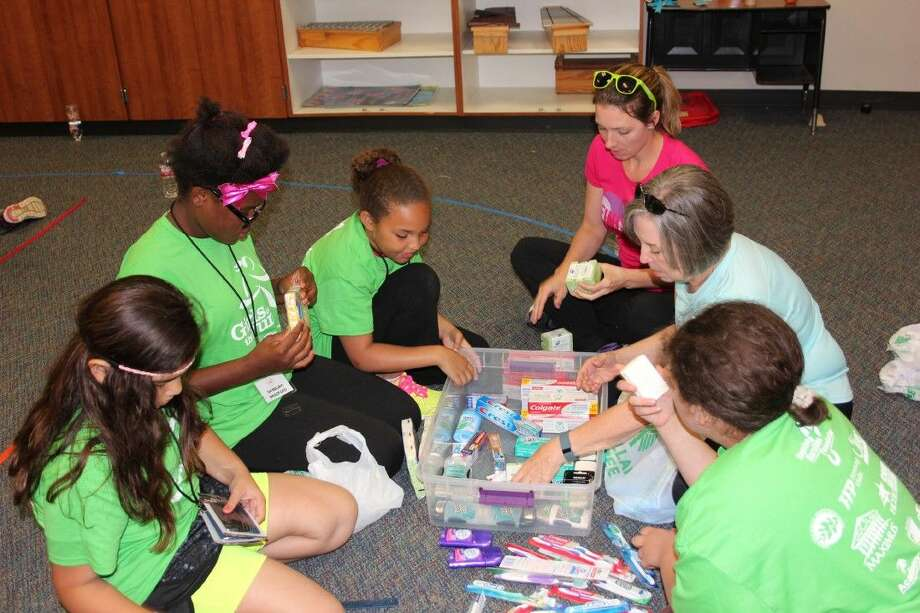 Heather Heidebreicht and Linda Sasser, volunteers with the Girls on the Run program, help create hygiene kits for the school counselor's office. It is one of the ways the girls learn about community service and other life lessons from the 10-week program.