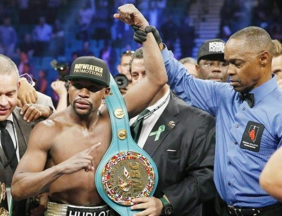 Floyd Mayweather Jr., celebrates his victory over Manny Pacquiao with the champion's belt.