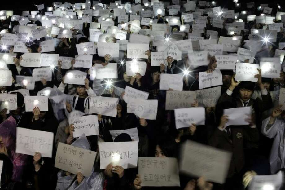 """Danwon High School students hold papers with messages such as """"come back,"""" """"miss you,"""" """"love you"""" and """"don't loose your hope"""" for their friends who are missing after Wednesday's ferry disaster at the school yard in Ansan, South Korea, Thursday, April 17, 2014. Strong currents, rain and bad visibility hampered an increasingly anxious search Thursday for 287 passengers, many thought to be high school students, still missing more than a day after their ferry flipped onto its side and sank in cold waters off the southern coast of South Korea. Photo: Woohae Cho"""