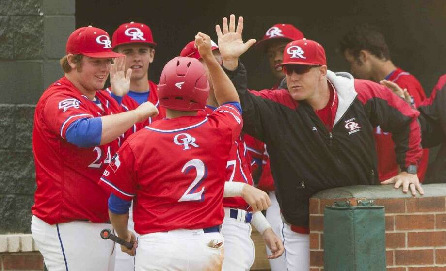 Oak Ridge players celebrate with Nick Calderaro after he scored on an RBI single by Addison Moss during the fifth inning a baseball game against Kingwood Park Saturday. Go to HCNpics.com to purchase this photo and others like it. Photo: Jason Fochtman