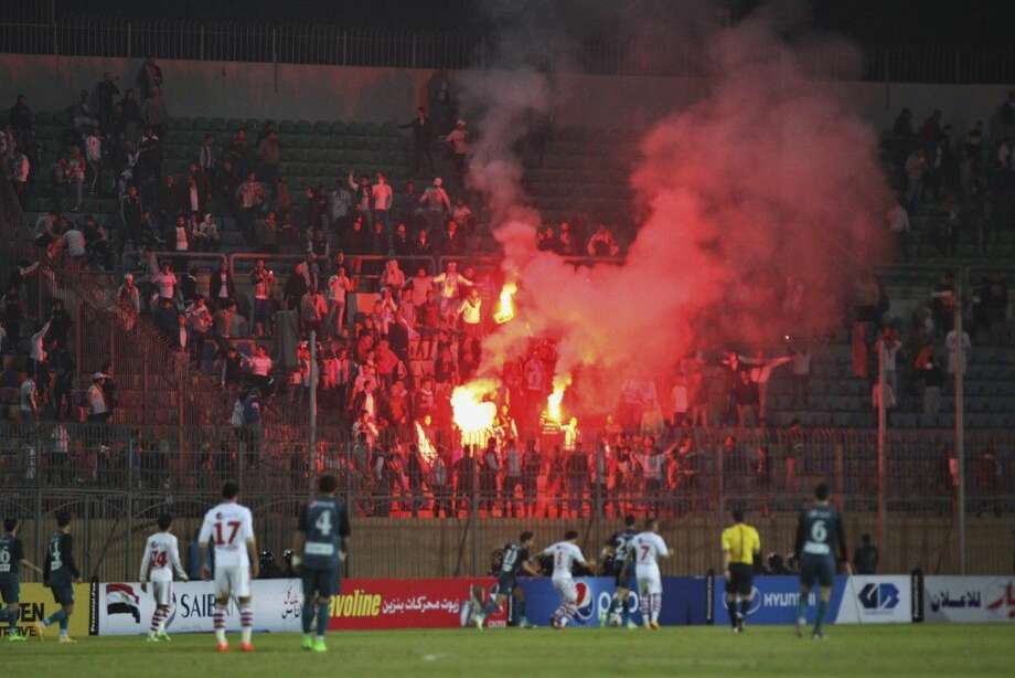 Soccer fans hold lit flares at the stand as they watch a match between Egyptian Premier League clubs Zamalek and ENPPI at Air Defense Stadium in a suburb east of Cairo, Egypt Sunday. Photo: Ahmed Abd El-Gwad
