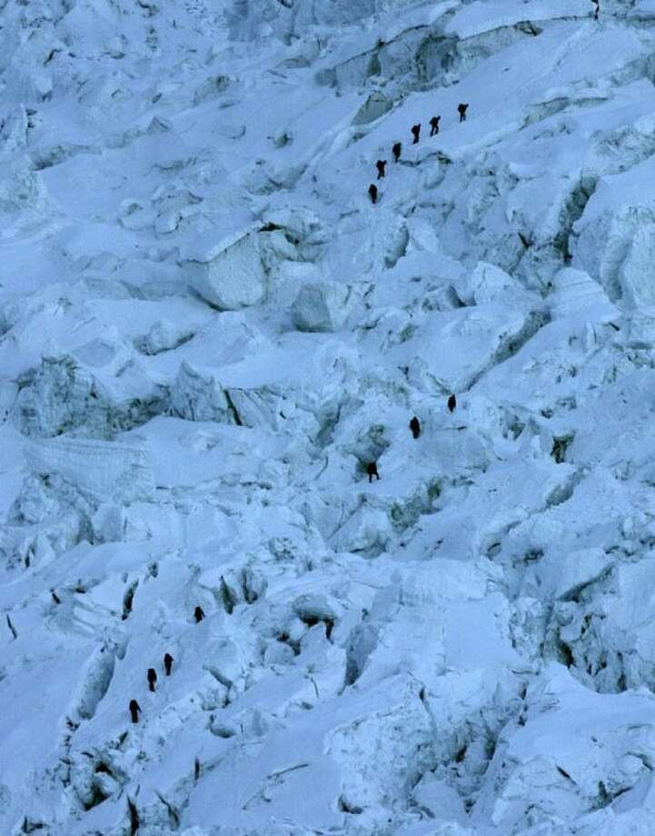 Mountaineers pass through the treacherous Khumbu Icefall on their way to Mount Everest base camp on May 18, 2003, in Nepal. An avalanche rocked Mount Everest early Friday, killing at least 12 Nepalese guides and leaving three missing in the deadliest disaster on the world's highest peak. Photo: Gurinder Osan