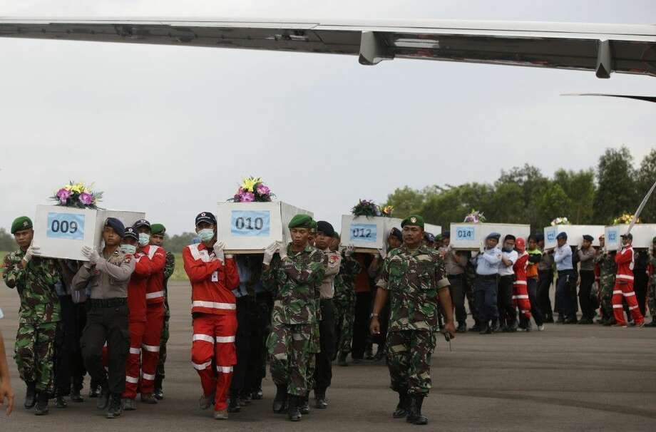 Members of the National Search and Rescue Agency carry coffins Friday containing bodies of the victims aboard AirAsia Flight 8501. Photo: Achmad Ibrahim