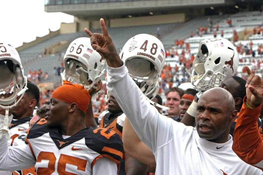 "Texas coach Charlie Strong gives the ""hook 'em horns"" sign while his players raise their helmets after the Orange and White spring football game Saturday in Austin. Photo: Michael Thomas"