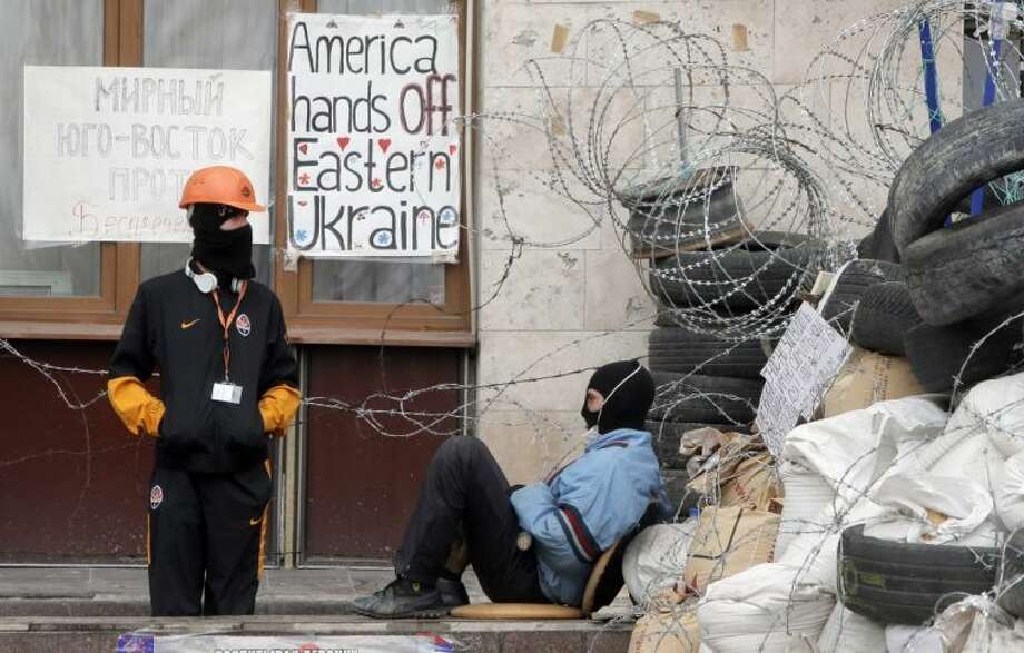 Masked pro-Russian activists guard a barricade at the regional administration building that they had seized earlier in Donetsk, Ukraine, Saturday. Pro-Russian insurgents defiantly refused Friday to surrender their weapons or give up government buildings in eastern Ukraine, despite a diplomatic accord reached in Geneva and overtures from the government in Kiev.