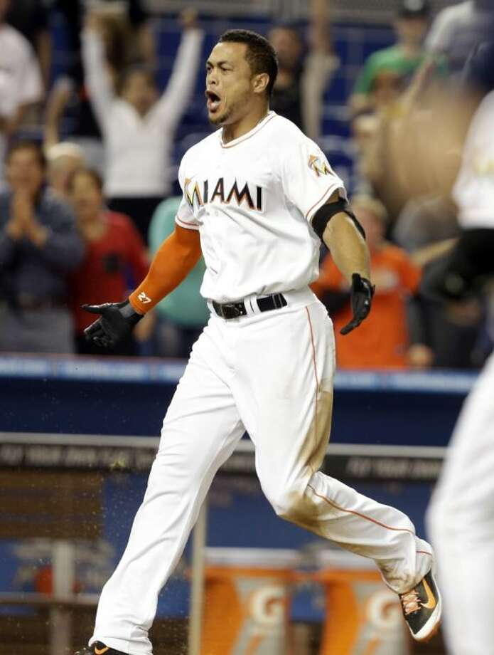 Miami Marlins slugger Giancarlo Stanton approaches home plate after hitting a grand slam in the ninth inning to defeat the Seattle Mariners 8-4 on Friday in Miami. Photo: Lynne Sladky