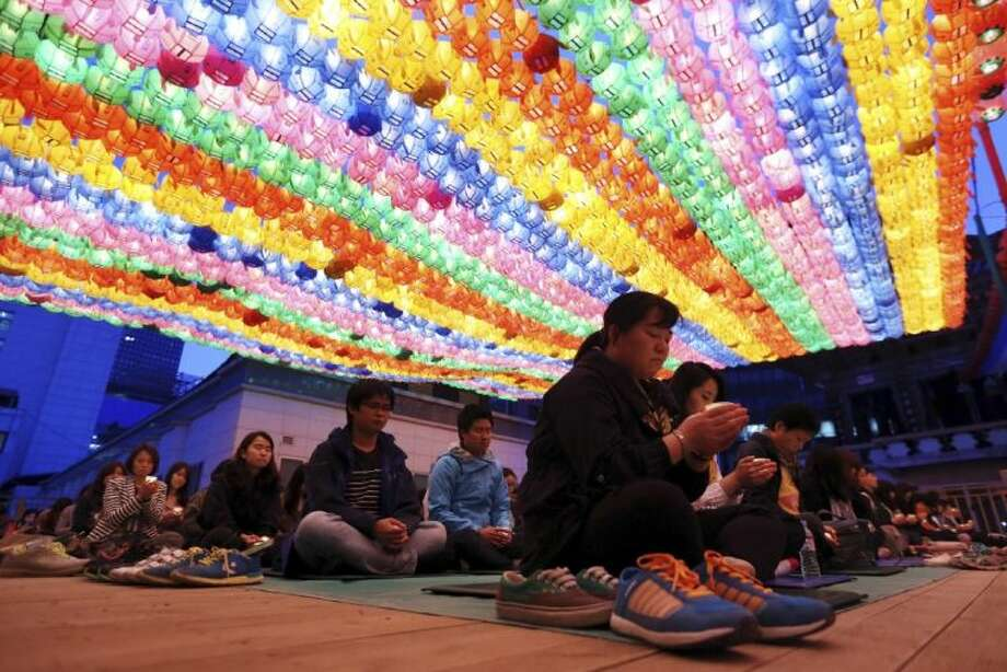 Buddhists pray during a service to wish for safe return of missing passengers aboard the sunken ferry Sewol, at Jogye temple in Seoul, South Korea, Saturday.