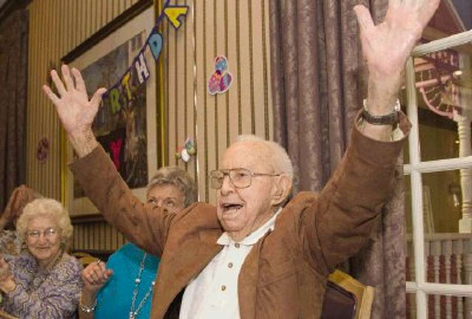 Jay Blume, Sr., who turns 104 today, raises his hands in joy during his birthday celebration at the Carriage Inn on Saturday. Family and friends celebrated Blume's birthday a day early this year with speeches, well-wishes, and birthday cards, a cake and presents. Blume continues to stay active by playing chess and exercising daily. Photo: Staff Photo By Ana Ramirez