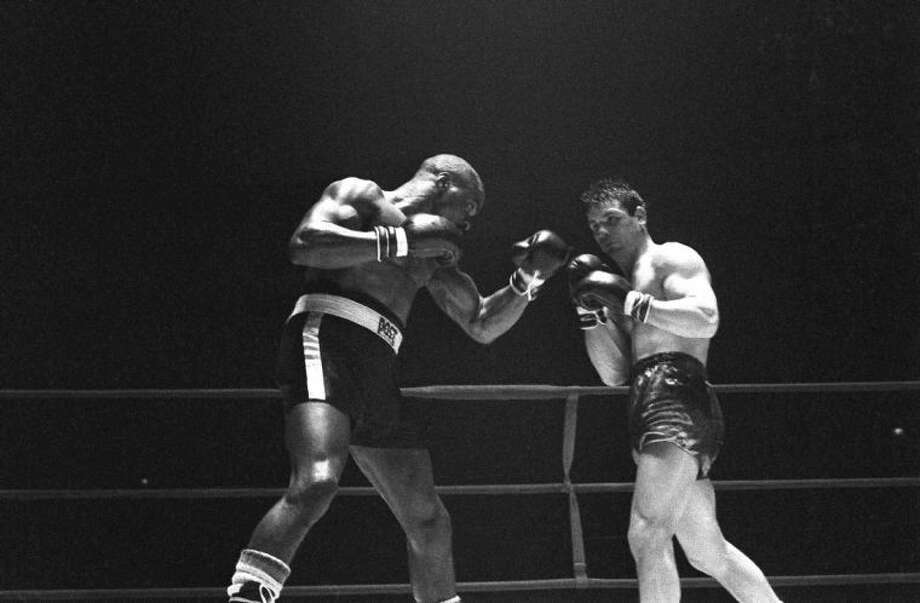 """In this Feb. 23, 1965 file photo, Rubin """"Hurricane"""" Carter, left, knocks out Italian boxer Fabio Bettini in the 10th and last round of their fight at the Falais Des Sports in Paris. Carter, who spent almost 20 years in jail after twice being convicted of a triple murder he denied committing, died at his home in Toronto, Sunday, April 20, 2014, according to long-time friend and co-accused John Artis. He was 76."""