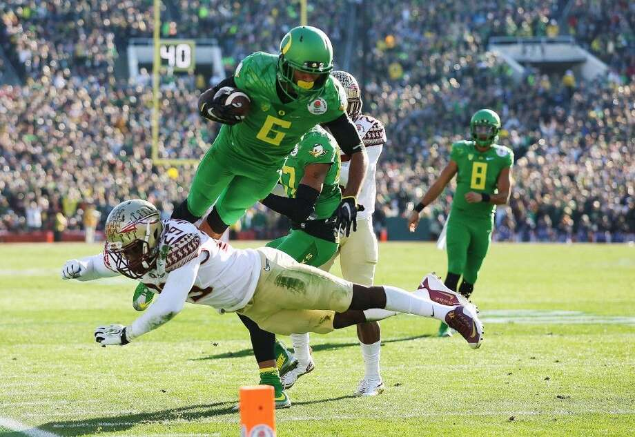 Oregon wide receiver Charles Nelson dives over Florida State defensive back Nate Andrews for a touchdown during the first half of the Rose Bowl on Thursday. Photo: Doug Benc