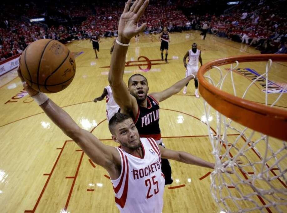 The Rockets' Chandler Parsons goes in for a shot as Portland's Nicolas Batum defends. Photo: David J. Phillip