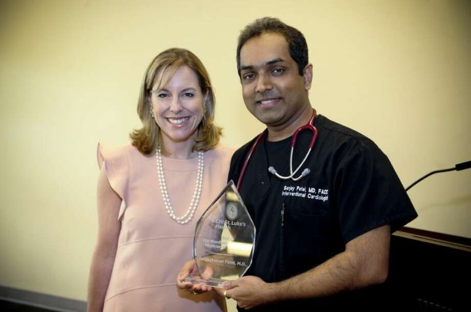"Sanjay Patel, M.D., cardiologist, right, was named the ""2014 Physician of the Year"" by St. Luke's The Woodlands Hospital and was honored by Debra F. Sukin, president, SLWH and St. Luke's Lakeside Hospital, and senior vice president of CHI St. Luke's Health. Photo: GUS SALINAS  S SLE   H GU S"