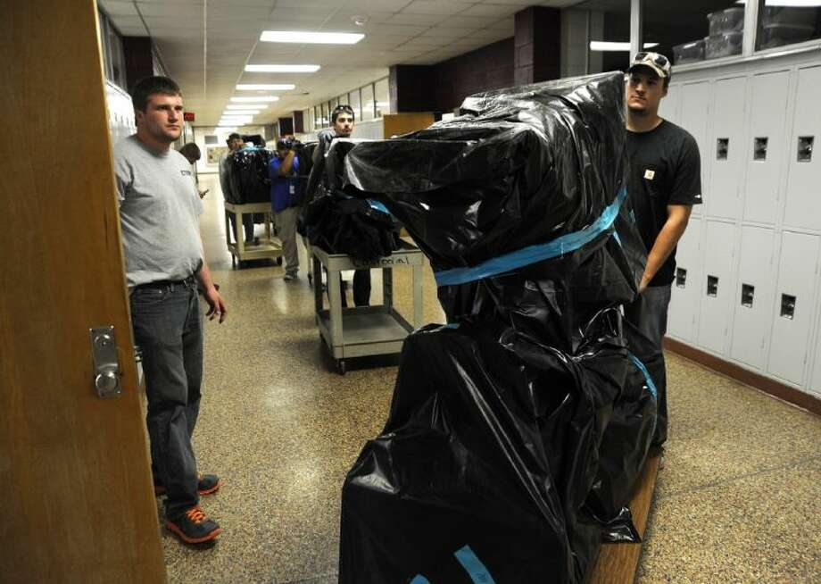 Employees with Allied International Emergency and Ector County Independent School District move desks and other items back into the classrooms in one of the last hallways to be cleared of mercury Thursday afternoon at John B. Hood Junior High. Students returned to class in parts of the school Thursday morning. Photo: Mark Sterkel|Odessa American