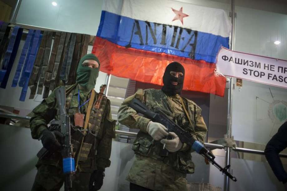 Masked pro-Russian gunmen guard an entrance of the Ukrainian regional office of the Security Service with a Russian National flag is in background in Luhansk, Ukraine, Monday. Photo: Alexander Zemlianichenko