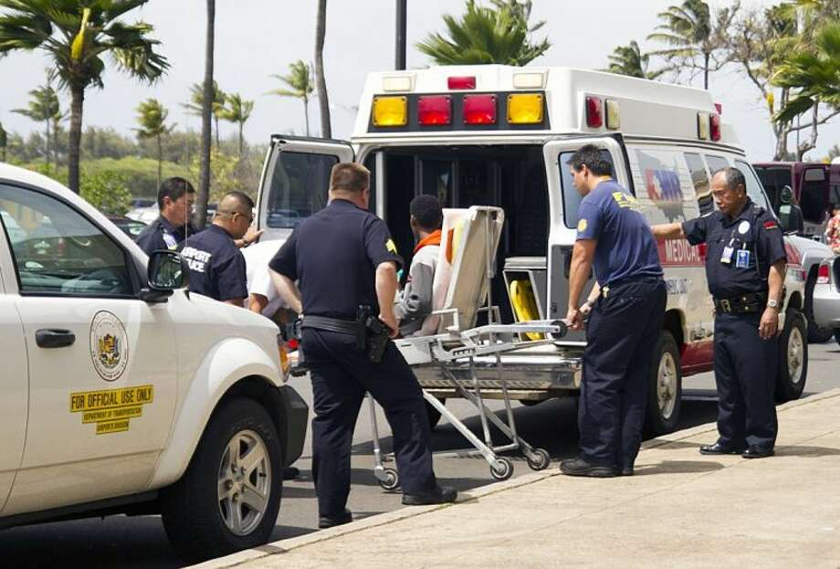 A 16-year-old boy, seen sitting on a stretcher center, who stowed away in the wheel well of a flight from San Jose, Calif., to Maui is loaded into an ambulance at Kahului Airport in Kahului, Maui, Hawaii Sunday afternoon, April 20, 2014. The boy survived the trip halfway across the Pacific Ocean unharmed despite frigid temperatures at 38,000 feet and a lack of oxygen, FBI and airline officials said. Photo: Chris Sugidono