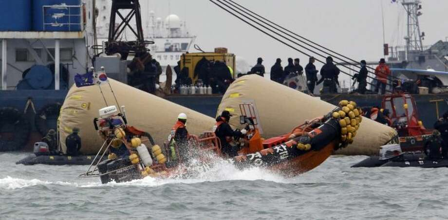 Searchers and divers look for people believed to have been trapped in the sunken ferry boat Sewol near the buoys which were installed to mark the vessel in the water off the southern coast near Jindo, south of Seoul, South Korea, Tuesday.
