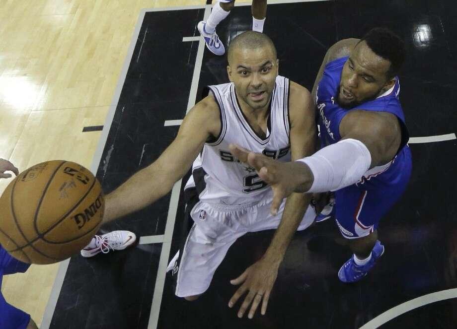 The Spurs' Tony Parker, left, shoots around the Los Angeles Clippers' Glen Davis. Photo: Darren Abate