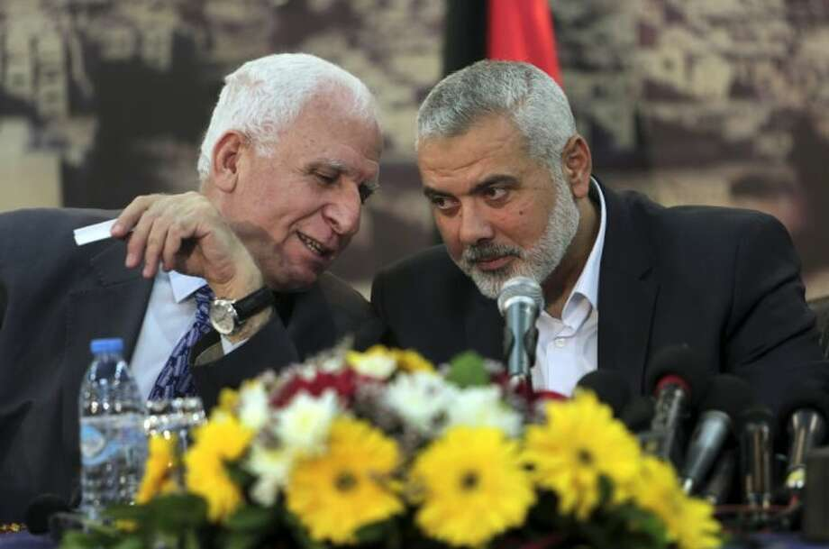 Senior Fatah official Azzam al-Ahmad, left, talks to Gaza's Hamas Prime Minister Ismail Haniyeh, during a press conference after the announcement of an agreement between the two rival Palestinian groups, Hamas and Fatah, at Haniyeh's residence in Shati Refugee Camp, Gaza Strip, Wednesday, April 23, 2014. Hamas and Fatah made a new attempt Wednesday to overcome the Palestinians' political split, saying they would seek to form an interim unity government within five weeks, followed by general elections by December at the earliest. Photo: Adel Hana