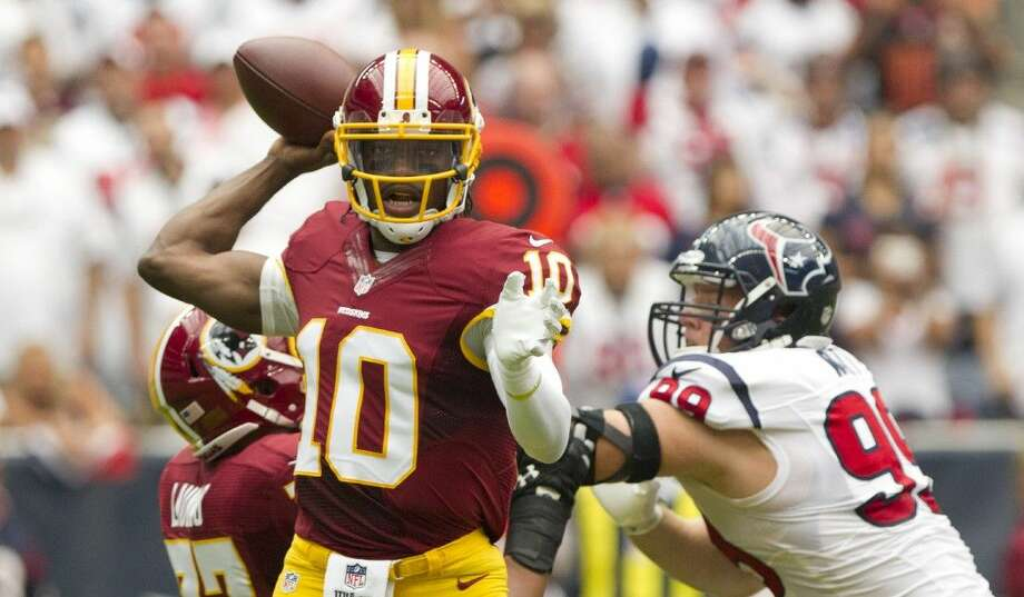 Washington Redskins quarterback Robert Griffin III (10) looks to pass as Houston Texans defensive end J.J. Watt (99) give pressure during the first half of an NFL football game Sunday, Sept. 7, 2014, in Houston. Photo: Jason Fochtman