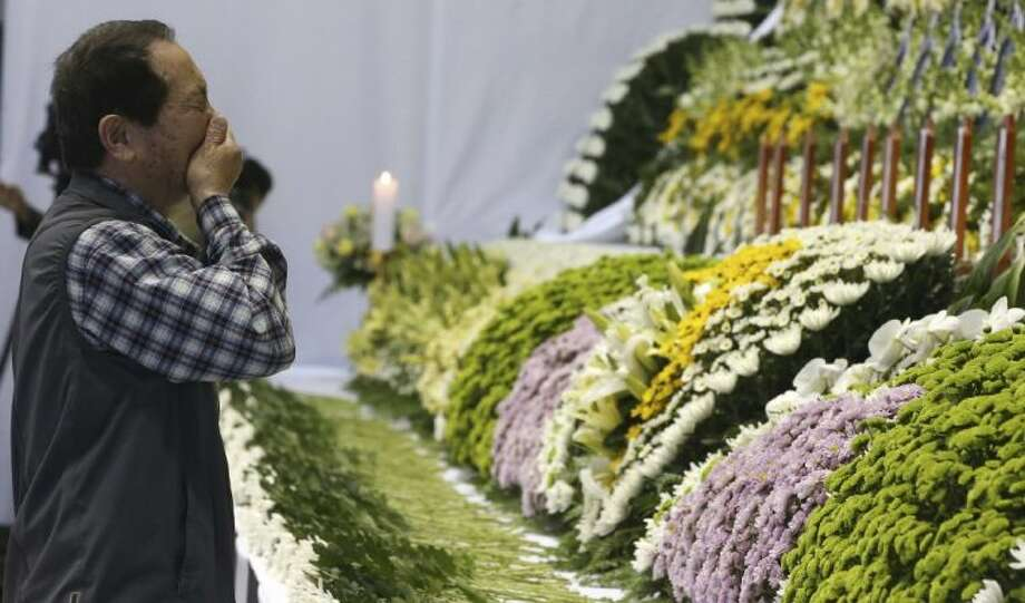 A mourner weeps as he pays tribute to the victims of the sunken ferry Sewol in the water off the southern coast at a gymnasium, in Ansan, South Korea, Wednesday, April 23, 2014. The victims are overwhelmingly students of a single high school in Ansan, near Seoul. More than three-quarters of the 323 students are dead or missing, while nearly two-thirds of the other 153 people on board the ferry Sewol when it sank one week ago survived. Photo: POOL